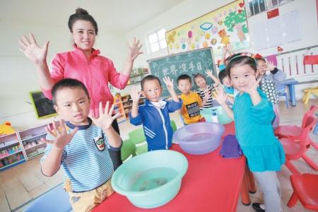 10月15日,在东港区营子幼儿园,老师在教小朋友们正确的洗手方法.