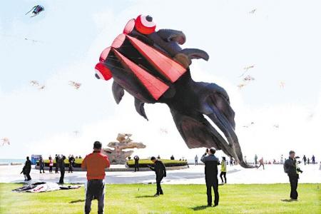 4月7日,风筝爱好者在日照·万平口海洋公园放飞巨型金鱼风筝.