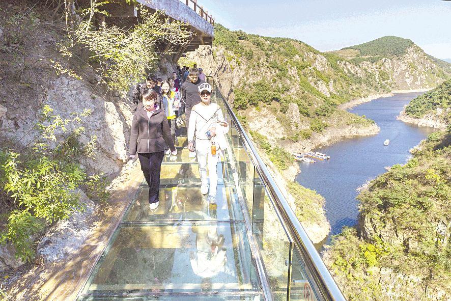 10月10日,在五莲县九仙山风景区,游客正在体验玻璃栈道的惊险与新奇